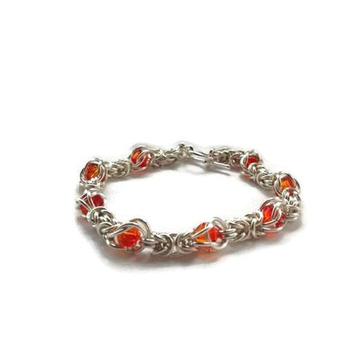 A handmade Byzantine weave chainmaille bracelet made with silver plated jump rings incorporating caged fire opal coloured Swarovski bicones and a silver plated toggle clasp. The bracelet measures 7 inches but I am able to adjust this if required, please just ask. A beautiful eye catching piece with lots of sparkle.  Your bracelet will be wrapped in tissue paper and placed in an organza bag.  Postage is First Class Signed For within the UK and I always obtain a proof of postage for each…