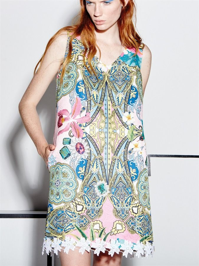 """Trapeze dress model, made of precious jacquard fabric with """"Hawaii"""" prints and decorated with macramé lace, flower applications and Swarovski crystals."""