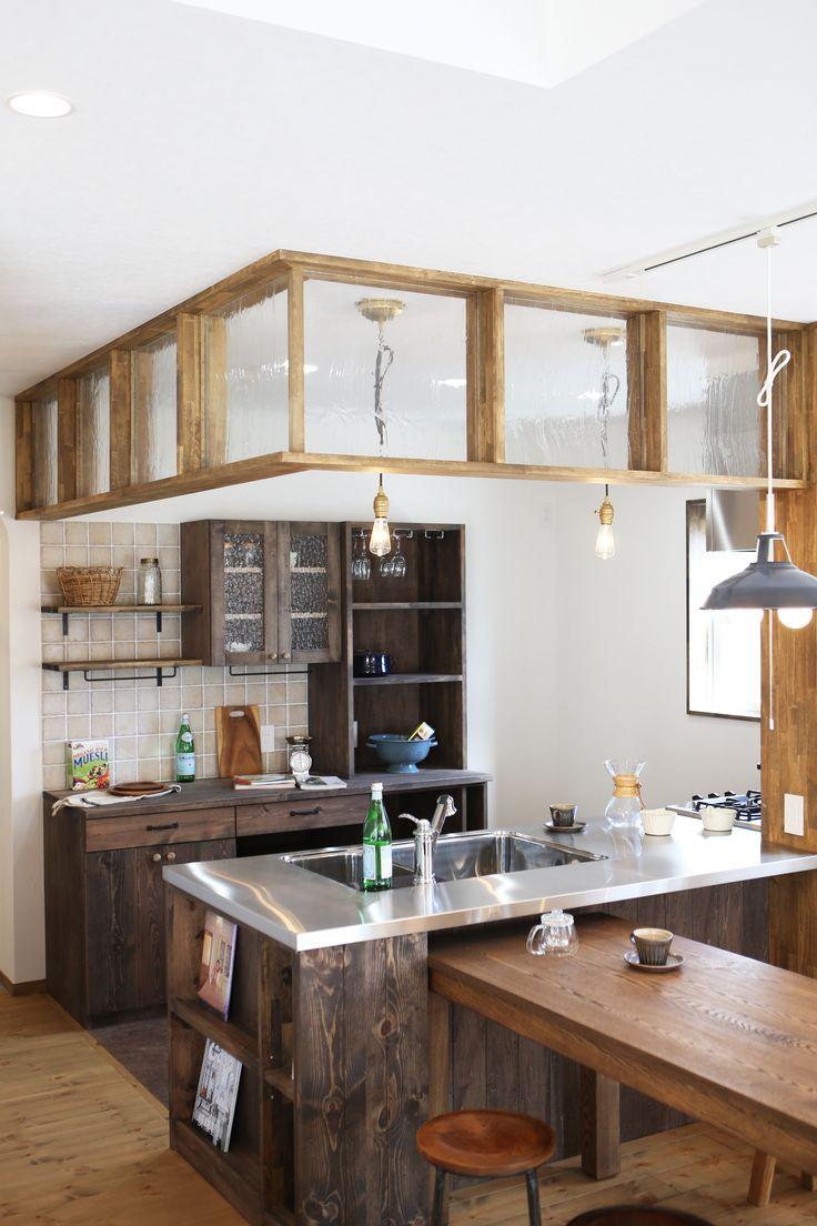 リビングに梁をあらわしにするため設けたキッチンの防火区画用の下がり壁。ただの壁だと圧迫感を感じますが、ガラス入り木フレームにすることで、抜け感が生まれ、独特な雰囲気に仕上がりました。