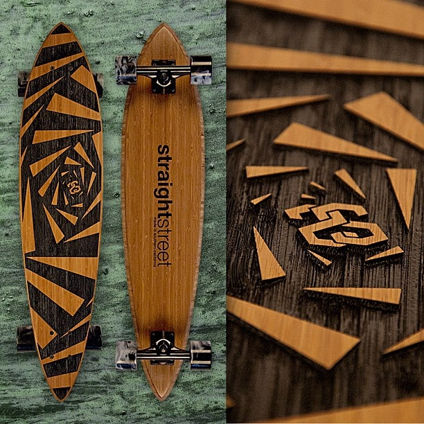 "The bamboo 34"" x 7.5"" pin-tail webby. Featuring hand carved artwork for grip on the top of the deck.     (Gator-y?)"