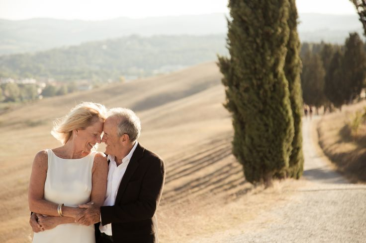 The couple during a walk in the countryside surrounded by cypresses