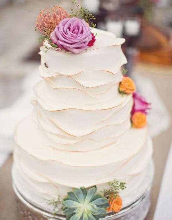 O ruffled cake é um bolo com textura de babados, que podem ser delicados e sutis ou bem contrastantes. Este modelo tem babados leves, que dão charme e romance à criação. Mais fotos de bolos de casamento aqui!