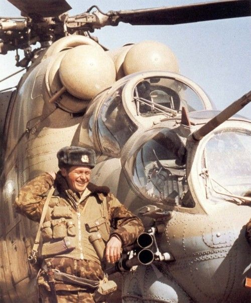 Soviet soldier next to a Mi-24P attack helicopter.