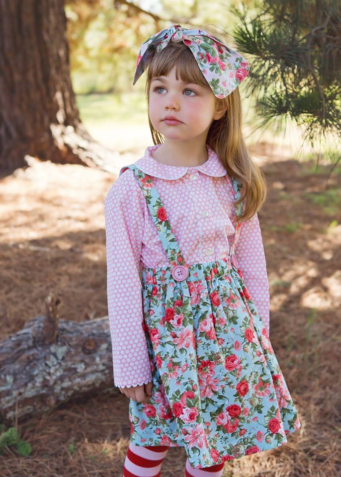 """Miss Stella is wearing the """"Little Dove"""" in Blue Roses paired with a Pink bubble dot Annie shirt. One of the coolest features of this sweet skirt is that the braces are REVERSIBLE and removable. So you can really play around with your styling!"""