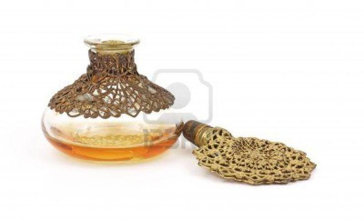 Een vintage parfumfles met ingewikkelde gouden filigraan stop naast glazen fles op een witte achtergrond. Stockfoto - 8797998