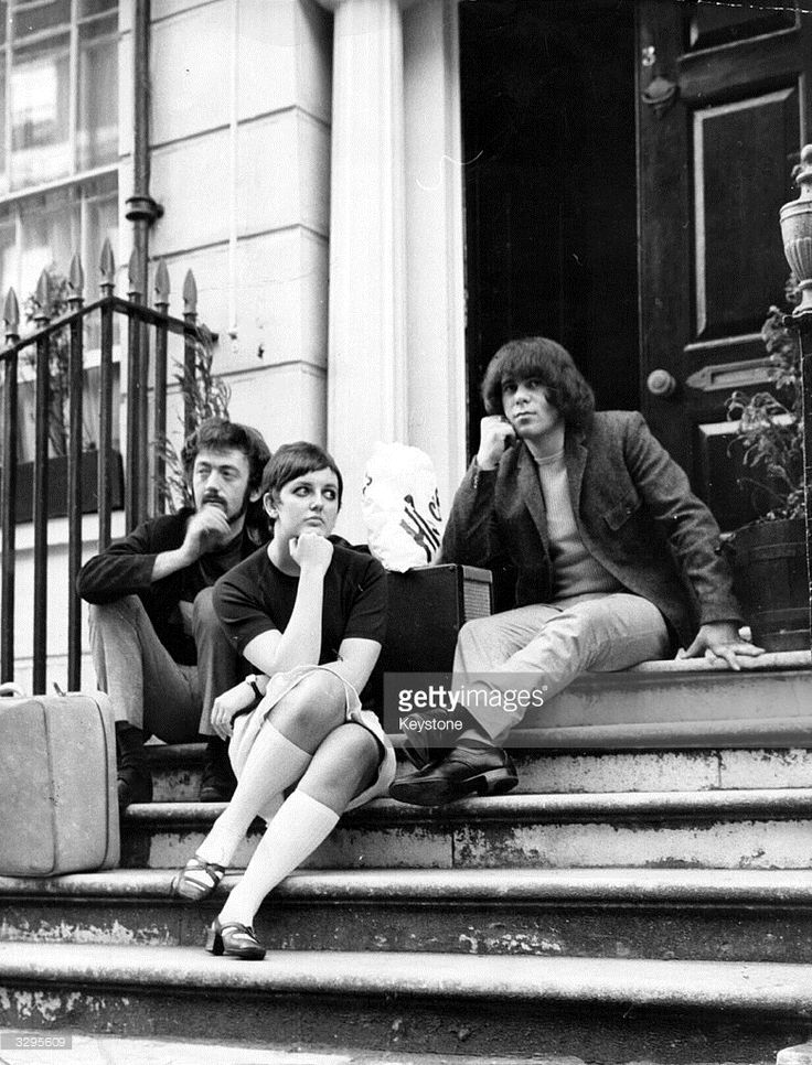 Two members of pop group The Pretty Things, guitarist Dick Taylor, left, and bass player John Stax, sit with their nineteen year old housekeeper Wendy Young on the steps outside their 40 guinea-a-week flat in Chester Road, Belgravia. Neighbours in the exclusive London area have complained one too many times and their landlord has told The Things to pack their bags. Only a few days ago a group of students renting a flat in Chester Road from Chancellor of the Exchequer Reginald Maudling were…