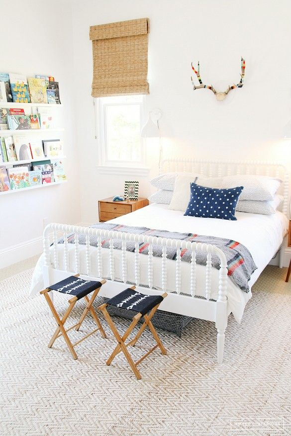 A kid's bedroom with colorful pillows and blanket, bookshelf, and faux deer antlers above bed