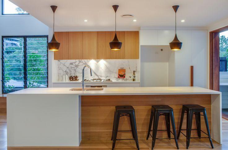 A kalka kitchen. Small lot home, Paddington Brisbane. Feature Blackbutt veneer cupboards, Statuoria marble splashback, Northern beach flooring, black feature pendants - Tom Dixon Beat Pendant.
