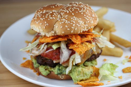 Taco burgers are basically hamburgers flavored with taco seasoning. The ground beef is mixed with taco seasoning, salsa, Doritos, salt and pepper. If you want to add a little heat, you can put some chopped jalapeno peppers into the hamburger mixture as well.