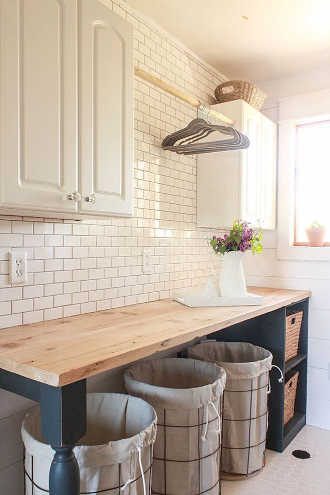 Gorgeous farmhouse laundry room with diy folding table with butler's block countertop, diy shiplap walls and white subway tile backsplash