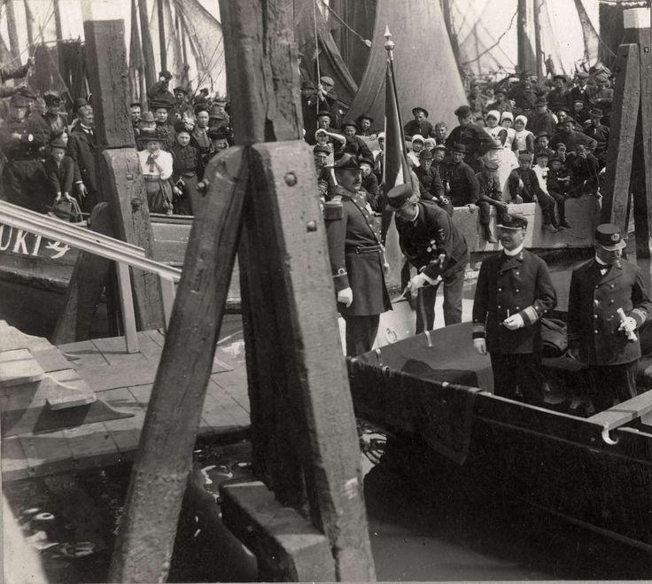 Prins Hendrik (in marine uniform en platte pet) brengt een bezoek aan de haven van Urk. De in klederdracht gestoken bevolking heet hem van harte welkom. 1911 #Urk