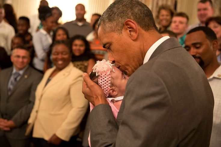"""2014: Year in Photos   The White House """"The President kisses a baby girl as he and the Vice President greeted wounded warriors and their families during their tour in the East Room of the White House."""" (Official White House Photo by Pete Souza)"""