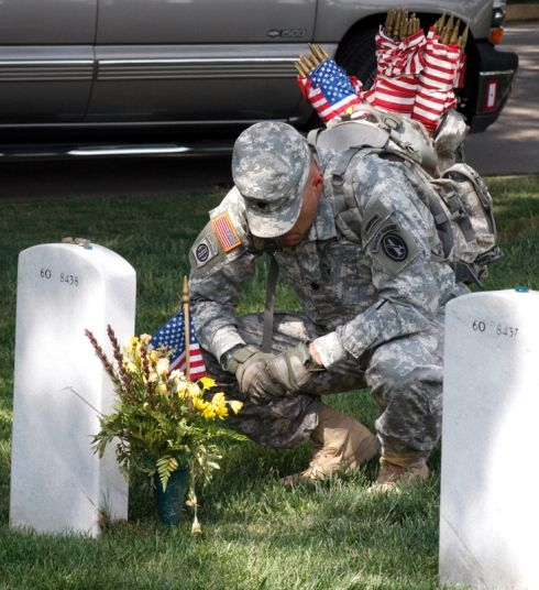 A soldier pauses after placing a flag at the grave of Army Maj. Douglas E. Sloan in Arlington National Cemetery's Section 60, where servicemembers killed in Iraq and Afghanistan are buried. Over 220,000 flags were placed at the cemetery Thursday in an annual Memorial Day weekend ceremony. Joe Gromelski/Stars and Stripes