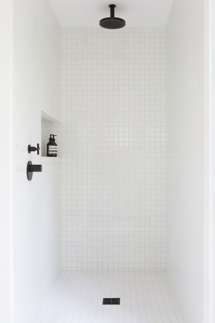Inexpensive white tile shower with black accents