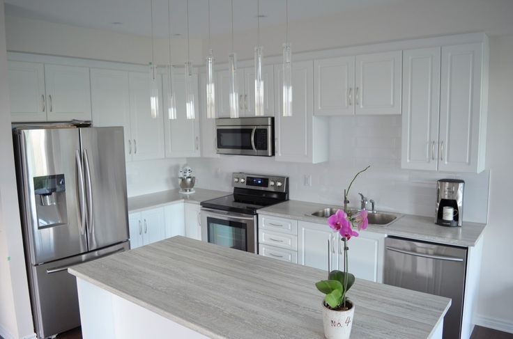 Open concept kitchen with island. Light colour laminate countertop. White Kitchen by Flawless Space