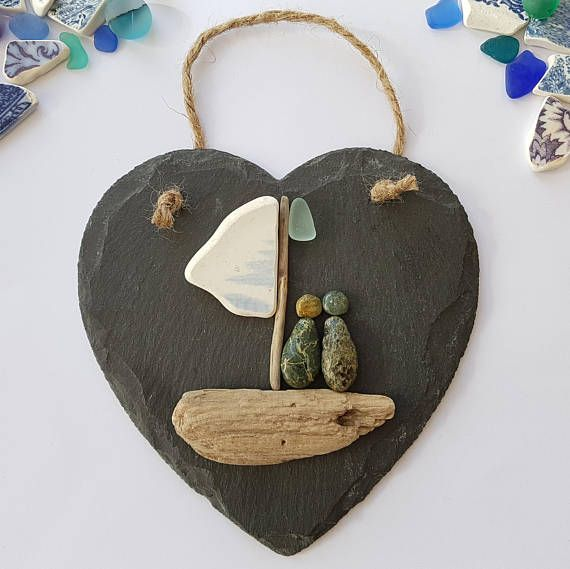 Made to order, I can re-create a near on identical pebble piece. This is a wonderful and unique handmade beach pebble art picture of pebble people sitting on a driftwood and sea pottery sail boat, with sea glass on a rustic slate heart. The rugged slate heart has a jute hanger and is