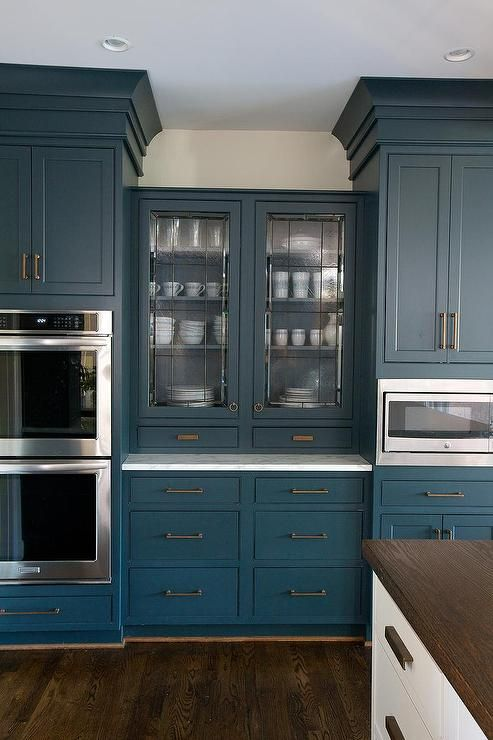 Lovely Kitchen Features Blue Cabinets Adorned With Brass Hardware Paired  With White Marble Countertop.