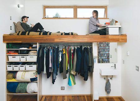 Sebuah kamar tidur rumah modern dengan tempat tidur dan meja kerja ditempatkan di atas rak penyimpanan, lemari dan wastafel!