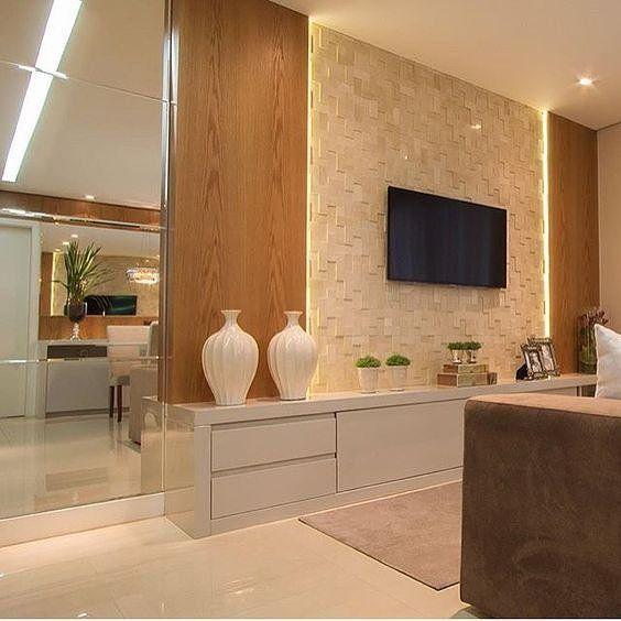 Sala de TV linda e inspiradora com móvel em laca branca e painel com revestimento de mosaico de pedras.