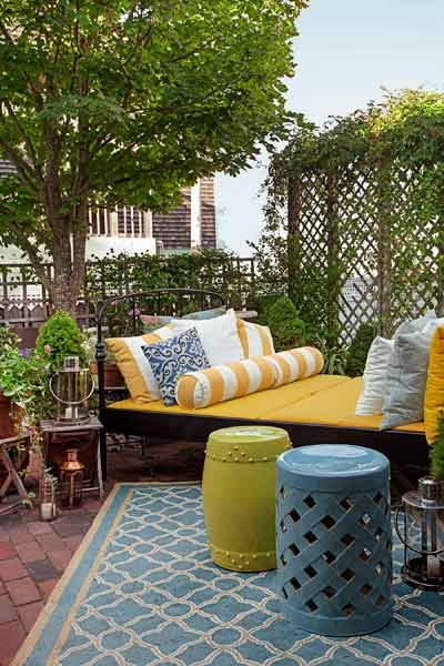 A double bed in weather-resistant black-painted iron is made comfy with an abundance of outdoor cushions. Ceramic garden stools stand ready to hold a cold drink, a book, or an extra party guest. | Photo: Eric Roth | thisoldhouse.com #OutdoorLiving