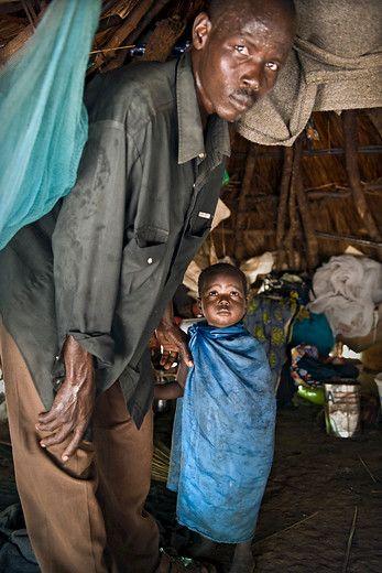 Christoph en zijn vader in hun tijdelijke onderkomen in het bos niet ver van het verbrandde dorp Bamatara. Het noorden van C.A.R. wordt al geruime tijd geteisterd door geweld. Rebellen, regeringsleger en bandieten maken het gebied onveilig. De burgerbevolking is het slachtoffer. foto: Sven Torfinn  www.vluchteling.nl