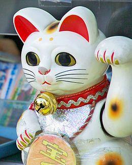 Manekineko.  Maneki (招き) vient du verbe maneku (招く) qui en japonais signifie inviter (dans le sens de faire venir) ou saluer, et neko (猫) désigne le chat. Il s'agit donc littéralement du « chat qui invite ». La patte levée varie selon que le chat est supposé attirer le client ou le faire dépenser plus d'argent dans le magasin : la patte gauche est censée attirer les clients, la patte droite l'argent. Il existe ainsi des chats levant les deux pattes et plus rarement les quatre pattes.