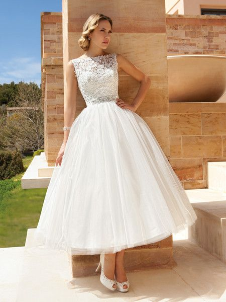 193 Sleeveless Cocktail length destination wedding dress featuring a Venice lace bodice with a sheer neckline and full tulle skirt. This bridal dress also has a belt with jeweled appliqué.