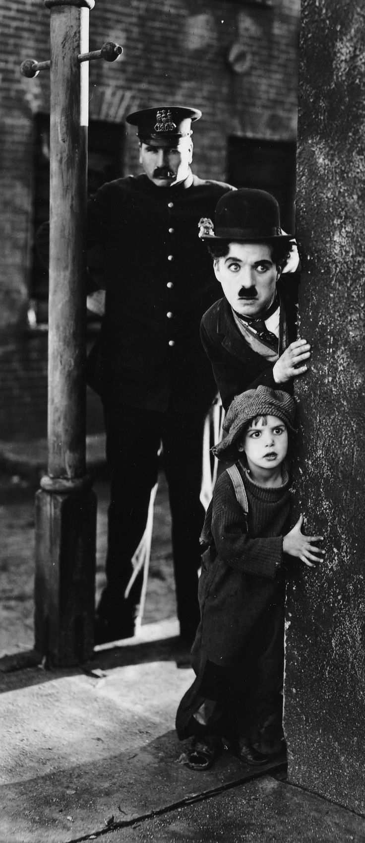 "Charlie Chaplin as The Tramp and Jackie Coogan (Uncle Fester on The Addams Family) as ""John"", The Kid, in the 1921 film ""The Kid"""