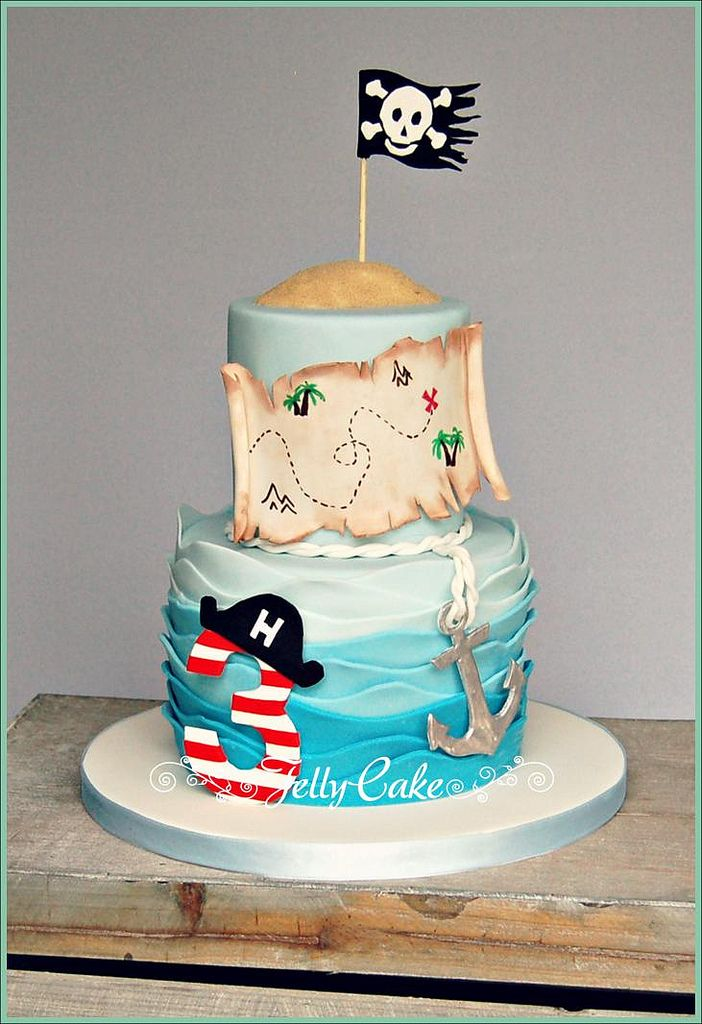 "This is the cake for my gorgeous Nephew's 3rd Birthday. He had a pirate themed party, so a pirate cake it had to be! A wavy sea with a sugar ""Pirate"" no. 3, sugar anchor and pirate map with the skull and crossbones flag blowing in the wind!"