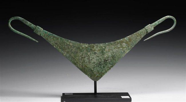 Greek bronze pectoral, Geometric Period,  7th century B.C. Triangular shaped pectoral  with hooked ends, such a piece would have been worn over chest with armor or in ceremonial situations, 30 cm wide. Private collection