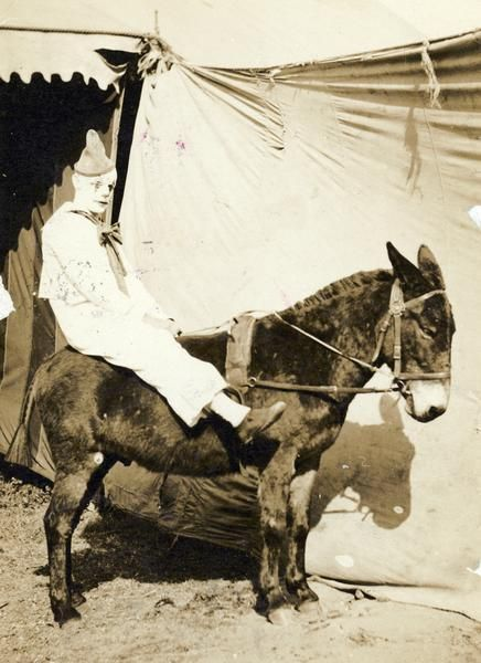 """A circus clown sits astride a donkey outside a tent."" (1909)"