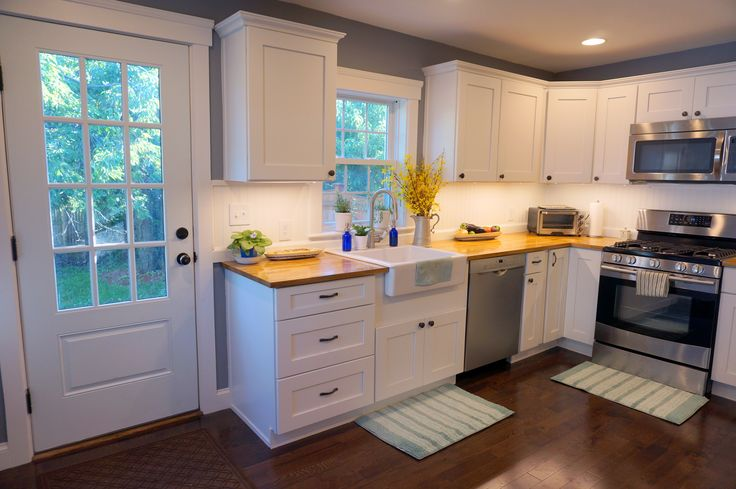 Farmhouse country kitchen. Butcherblock counters with Waterlox. Ikea apron sink. Hardwood floors. Undercabinet lighting. White kitchen with beadboard.