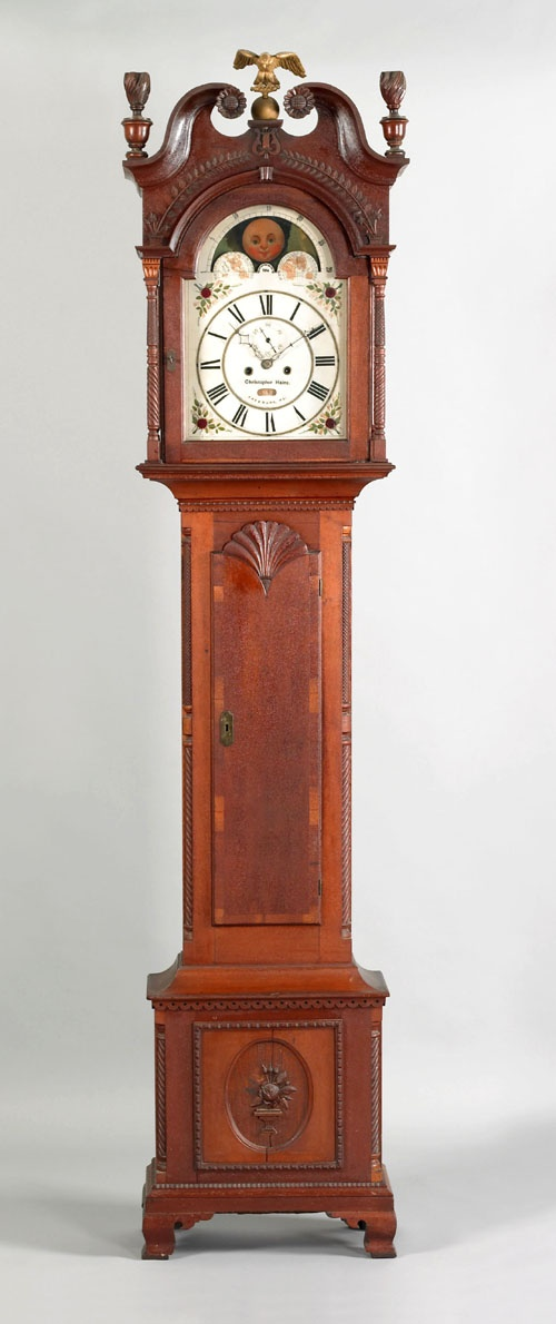 "Snyder County, Pennsylvania, Federal cherry tall case clock, early 19th c., the broken arch bonnet with unusual frieze with applied potted floral vines, over a 30-hr. works with later inscription ""Christopher Haines Freeburg, PA"". above an elaborately carved case supported ba ogee bracket feet, 96 H."
