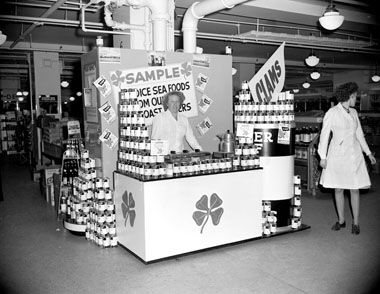 """Two women staff a display booth at Woodward's department store in Vancouver offering samples of BC Packers canned clam products, 1940s. Notice the prominent """"Clover Leaf"""" display.City of Vancouver Archives. #vintage #1940s #Canada #department_stores #grocies #food"""