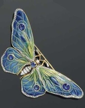 AN ART NOUVEAU ENAMEL, DIAMOND, SAPPHIRE AND RUBY BROOCH, ca. 1890. Designed as a butterfly, the wings mounted en tremblant, the body set with one oval sapphire and old-mine-cut diamonds. The wings decorated with plique-à-jour enamel in blue-green tones, and set with four sapphire cabochons. The wing borders partially set with rose-cut diamonds. Probably of French. #ArtNouveau #brooch