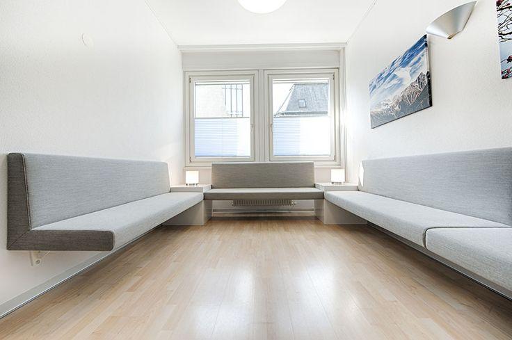 Reduziertes Interieur nach Kundenwunsch: Wartezimmer mit komfortabler Sitzbank, die zum Verweilen und Warten einlädt.