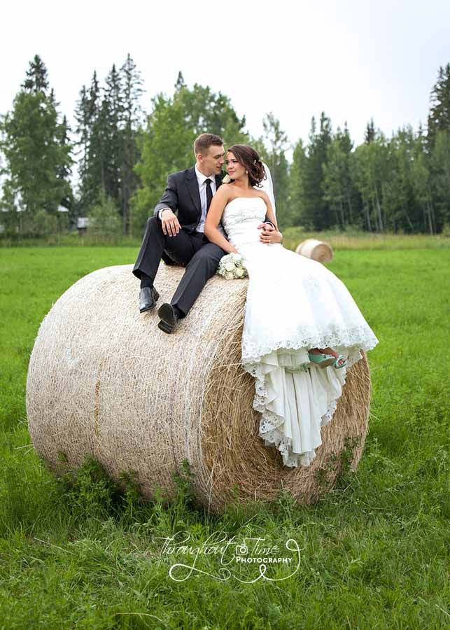 Love on a hay bale. A newly married couple, enjoy a moment together while sitting atop a large round hay bale. Wedding photography by Throughout Time Photography, #Quesnel, #British Columbia, #love, #marriage, #couple in love, #newly weds, #wedding gown, #suit, #groom, #bride, #sitting, #in love, #field, #summer, #talking, #sharing a moment, #quiet moment, #wedding formal photography, #bride and groom photo shoot ideas, #fun wedding ideas, #summer wedding ideas, #photo shoot with hay bales,