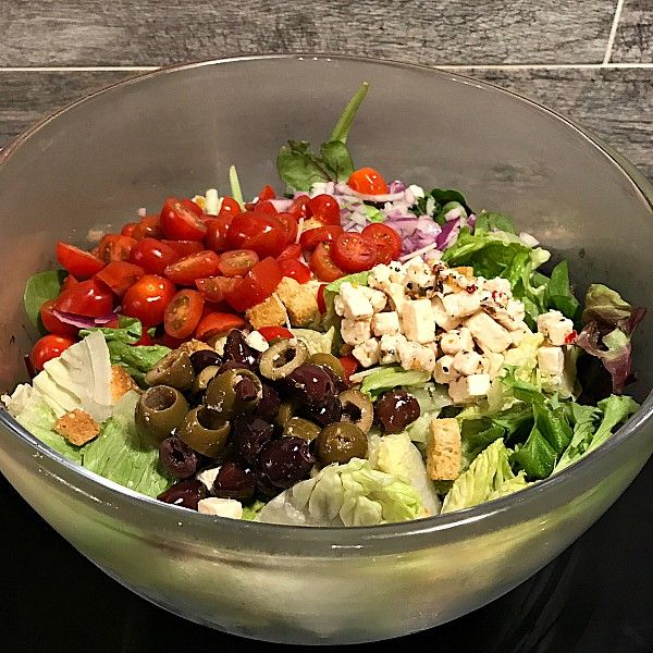 This Easy Greek Feta Salad Recipe recipe is made with fresh romaine lettuce, red onion, tomatoes, and DeLallo's Greek Feta Salad Mix - the perfect salad!
