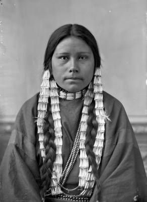 Two Bear's daughter, Dakota woman, 1/2 length studio portrait with painted backdrop, wearing braided hair with ornamentation, dentalium shell earrings & necklaces. Dated: 188?  What is her name and where was this photo taken?