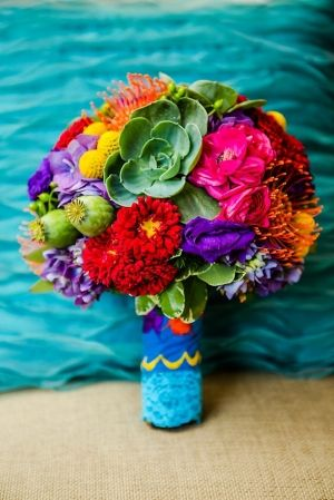 Red asters, purple lissies, billy buttons, succulents, hydrangeas, orange pincushion protea, pink ranunculus, poppy pods
