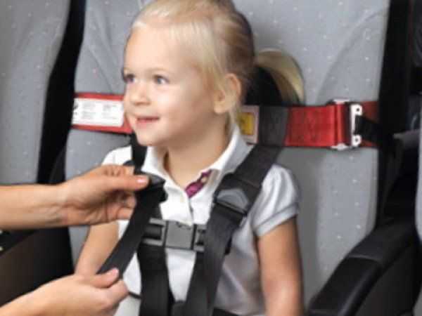 CARES - Child Harness Aviation Restraint System, Kids Fly Safe.  They say the FAA approves it to be used on airplanes and it doesn't interfere with the tray table of the person sitting behind it.