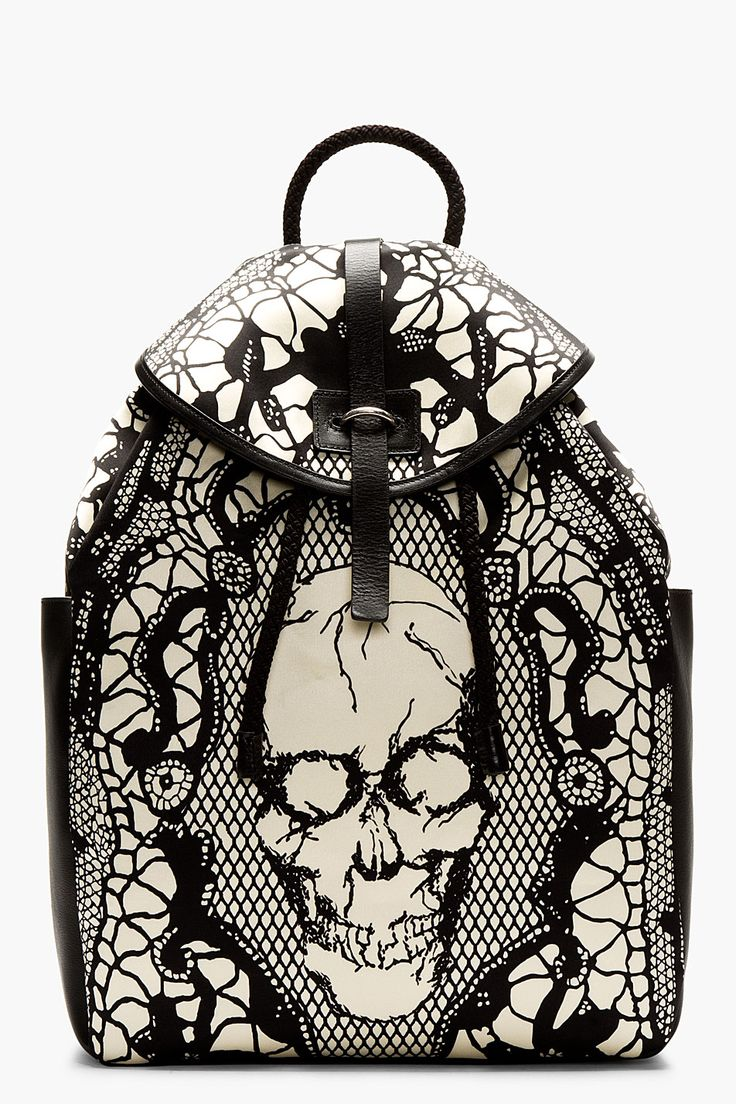 Structured buffed leather backpack in black and ivory. Lace and skull print throughout. Silver-tone hardware. Foldover flap at main compartment with tab-slot closure.  http://zocko.it/LD2rc