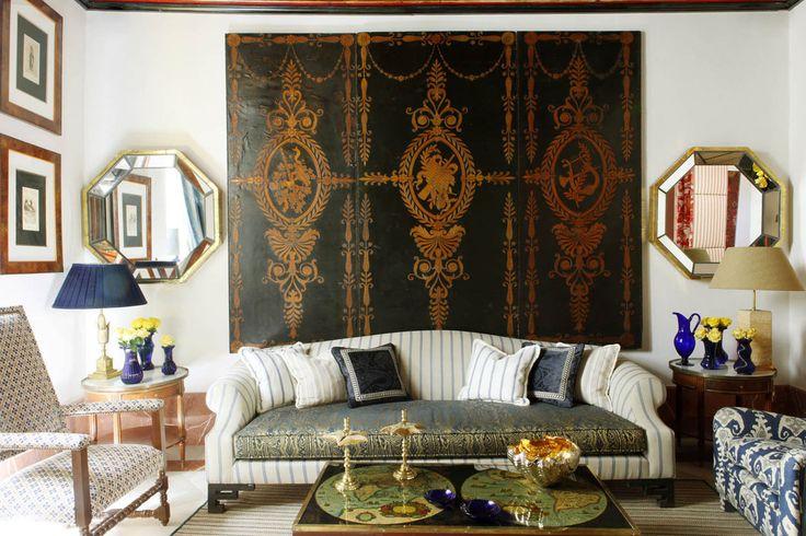 Pair of Spanish 17th-century mirrors; Spanish 17th-century armchair on left; Modern English armchair on right upholstered in Jim Thomson fabric.   - Veranda.com