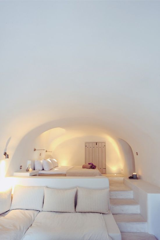 Mobilier maçonné et murs se confondent, formes organiques et blanc omniprésent, jeu de niveaux. Le dépouillement d'une maison méditerranéenne.