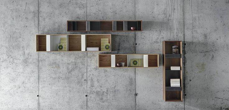 una serie di elementi contenitori da appendere a parete, di forte impatto grafico per ritmica proporzione di pieni e vuoti e sottigliezza dei materiali. I contenitori sono realizzati in legno massello di noce o castagno di mm13 di spessore, all'interno, gli elementi divisori funzionali e decorativi, sono in lamiera d'acciaio piegata. Disponibili in diverse misure, orizzontali o verticali, possono assumere molteplici funzioni, da libreria a portaoggetti per le zone living e cucina...