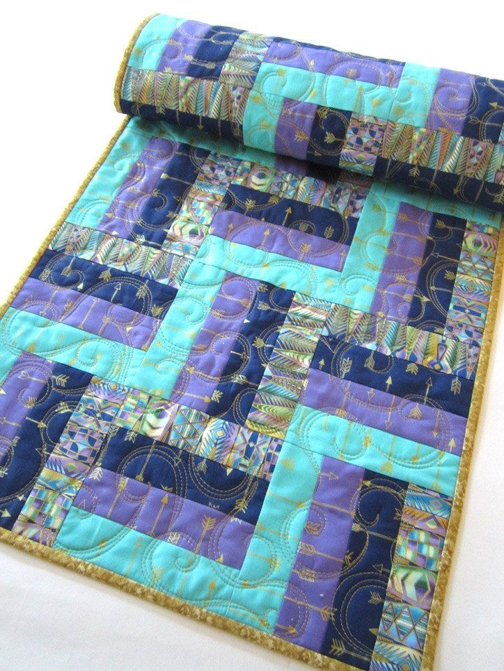 This table runner is made using blue, aqua and purple fabrics with arrows imprinted with a gold metallic. There is some gold metallic in all the fabrics. This runner will be a beautiful setting for yo