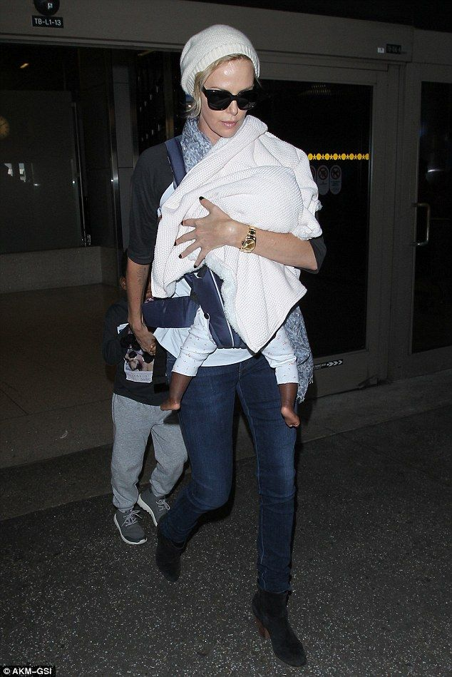 Hands-on mom: Charlize Theron touched down in Los Angeles on Tuesday with her two children after flying in from Germany