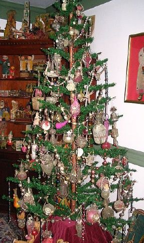 Six foot German feather tree decorated with 1881 - 1920 wire wrapped ornaments.  Antique German toys in 1800 cupboard.