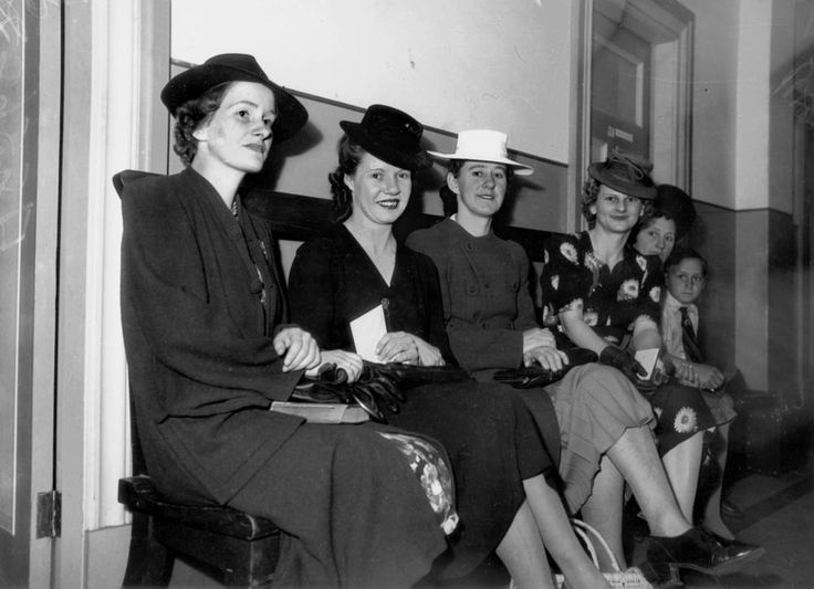Women applicants waiting for medical tests at Town Hall, Brisbane, 1942. Waiting women have applied for work as tram conductors during World War II. Left to right: Mrs A. C. Cox, Miss R. Higgins, Mrs V. Mann, Mrs E. Holmes. (Description supplied with photograph).