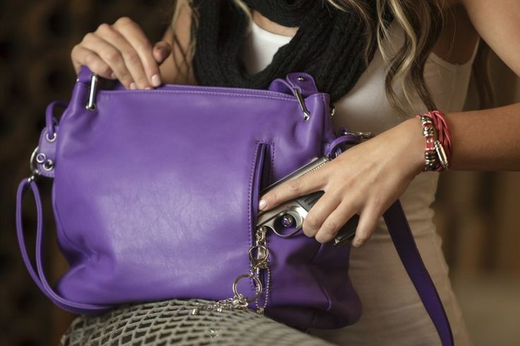"Item #: PU-0040 - Urban Moxy ""Aurora"" Purple Concealed Carry Purse. The Urban Moxy Aurora is an eye catching, yet classy purple bag that boasts a stunning chain accent and a braid on the side. The texture is extremely smooth and the bag not only looks good, it's comfortable to carry. Some of the features include; rivets on the bottom to protect the bag when it is set on the floor, a detachable shoulder strap and two elbow straps. Just like whole line of Urban Moxy concealed carry purses, the…"